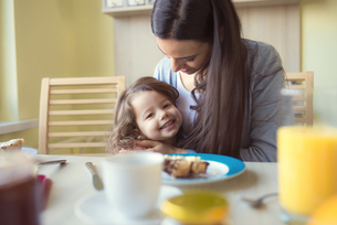 Portrait of smiling little girl and her mother at breakfastの写真素材 [FYI04342389]