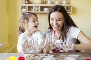 Portrait of laughing mother and her little daughter baking tの写真素材 [FYI04342394]