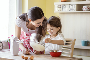 Portrait of smiling little girl and her mother baking togethの写真素材 [FYI04342396]