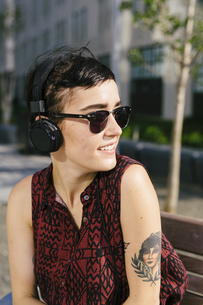 Portrait of tattooed young woman with headphones and sunglasの写真素材 [FYI04342423]