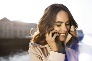 Germany, Berlin, young woman on the phone at River Spreeの写真素材 [FYI04342457]