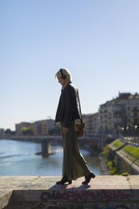 Italy, Verona, fashionable blond woman walking on a wall lisの写真素材 [FYI04342489]