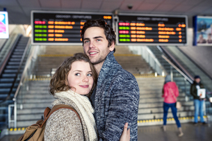 Smiling young couple embracing in station concourseの写真素材 [FYI04342503]