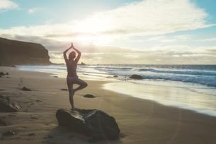 Spain, Fuerteventura, El Cotillo, back view of woman practicの写真素材 [FYI04342516]