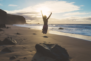 Spain, Fuerteventura, El Cotillo, back view of woman jumpingの写真素材 [FYI04342517]