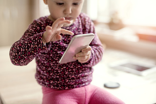 Toddler playing with smartphoneの写真素材 [FYI04342522]