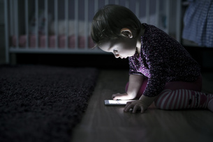 Toddler sitting on the floor playing with smartphoneの写真素材 [FYI04342524]
