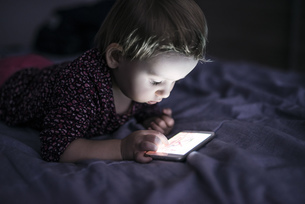 Toddler lying on  bed playing with smartphoneの写真素材 [FYI04342527]