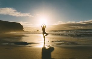 Woman practicing yoga on the beach at sunsetの写真素材 [FYI04342534]