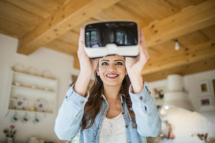 Young woman at home using Virtual Reality gogglesの写真素材 [FYI04342583]