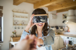 Young woman at home using Virtual Reality gogglesの写真素材 [FYI04342584]