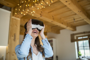 Young woman at home using Virtual Reality gogglesの写真素材 [FYI04342585]