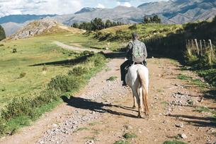 Peru, Cusco, back view of man riding horseの写真素材 [FYI04342604]