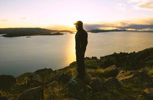 Peru, Amantani Island, man enjoying sunset from Pachamama peの写真素材 [FYI04342610]