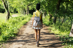 Back view of young woman with backpack in natureの写真素材 [FYI04342631]