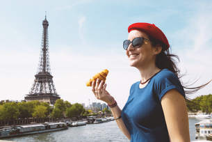 France, Paris, woman with croissant standing in front of Seiの写真素材 [FYI04342644]