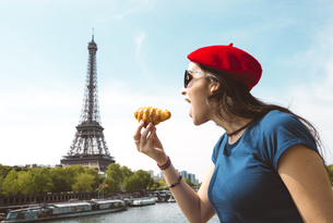 France, Paris, woman eating croissant in front of Seine riveの写真素材 [FYI04342645]