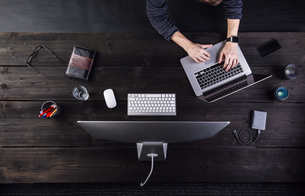 Man working at desk with computer and various digital gadgetの写真素材 [FYI04342646]