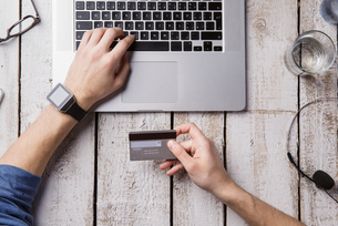 Man sitting at desk paying online with credit cardの写真素材 [FYI04342651]