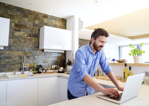 Man working in kitchen using laptopの写真素材 [FYI04342653]