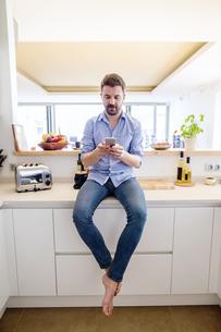 Man sitting in kitchen using smart phoneの写真素材 [FYI04342654]