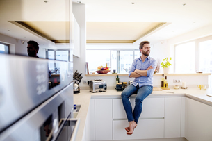 Man sitting in kitchen with arms crossedの写真素材 [FYI04342655]