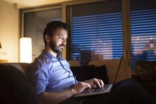 Man sitting on sofa, using laptopの写真素材 [FYI04342662]