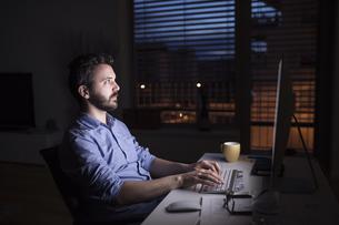 Man working at night, using computerの写真素材 [FYI04342663]