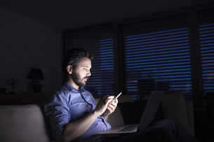 Man working at night using smart phone and laptopの写真素材 [FYI04342664]