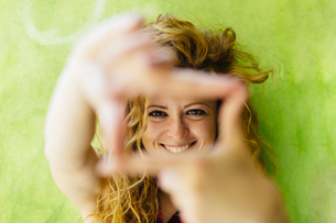 Portrait of smiling woman shaping a finger frameの写真素材 [FYI04342681]