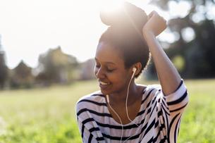 Smiling woman hearing music with earphonesの写真素材 [FYI04342693]