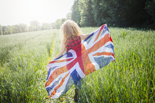 Back view of woman with Union Jack in natureの写真素材 [FYI04342701]