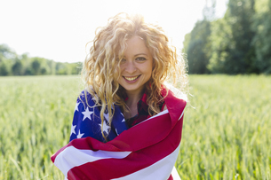 Portrait of smiling woman with American Flag in natureの写真素材 [FYI04342704]