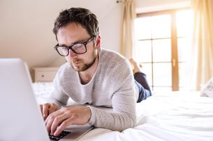 Man lying on bed using laptopの写真素材 [FYI04342711]