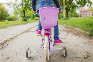 Girl riding bicycle with training wheelsの写真素材 [FYI04342719]