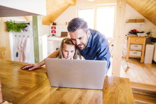 Father and daughter using laptop at homeの写真素材 [FYI04342765]