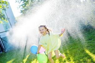 Little girl having fun with lawn sprinkler in the gardenの写真素材 [FYI04342842]