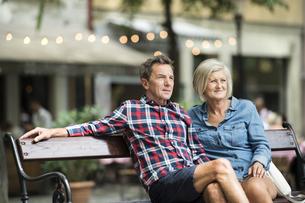 Senior couple sitting on bench watching somethingの写真素材 [FYI04342887]