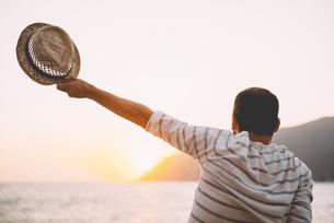 Greece, Cylcades Islands, Amorgos, man holding straw hat enjの写真素材 [FYI04342901]