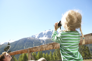 Girl looking through binoculars on panorama terrace in the mの写真素材 [FYI04342911]