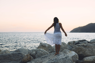 Back view of a woman standing on a rock in front of the seaの写真素材 [FYI04342956]