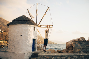 Greece, Amorgos, Aegialis, back view of man holding the bladの写真素材 [FYI04342960]
