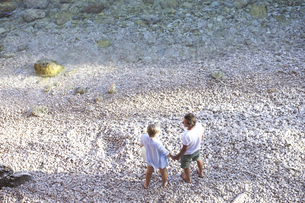 Top view of senior couple standing hand in hand on the beachの写真素材 [FYI04342984]