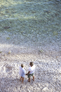 Top view of senior couple standing hand in hand on the beachの写真素材 [FYI04342986]