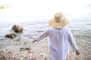 Back view of woman wearing straw hat standing at seafrontの写真素材 [FYI04342987]