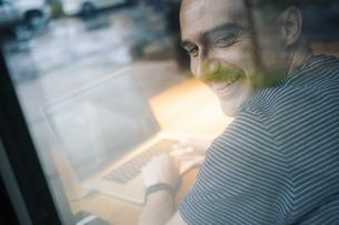 Smiling man using laptopの写真素材 [FYI04342992]