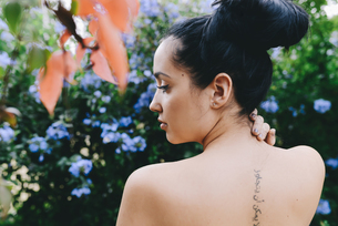 Woman with an arabic tattoo on her back surrounded by flowerの写真素材 [FYI04343020]