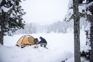 Senior man camping in snow-covered landscapeの写真素材 [FYI04343035]