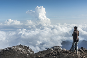 Italy, Sicily, hiker standing on Mount Etna looking at viewの写真素材 [FYI04343103]