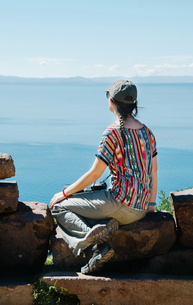 Peru, Taquile, back view of woman sitting on a rock enjoyingの写真素材 [FYI04343250]